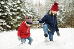 Two adorable little girls having fun together in beautiful winter forest. Beautiful sisters playing in a snow. royalty free stock photo