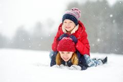 Two adorable little girls having fun together in beautiful winter park. Beautiful sisters playing in a snow. royalty free stock image