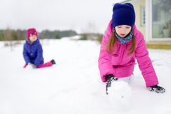 Two adorable little girls having fun together in beautiful winter park. Beautiful sisters playing in a snow. royalty free stock images