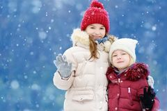 Two adorable little girls having fun together in beautiful winter park. Beautiful sisters playing in a snow. Winter activities for kids Royalty Free Stock Images