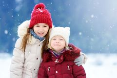 Two adorable little girls having fun together in beautiful winter park. Beautiful sisters playing in a snow. stock photos