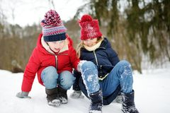 Two adorable little girls having fun together in beautiful winter park. Beautiful sisters playing in a snow. royalty free stock photo