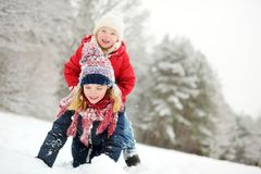 Two adorable little girls having fun together in beautiful winter park. Beautiful sisters playing in a snow. royalty free stock photography