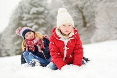 Two adorable little girls having fun together in beautiful winter park. Beautiful sisters playing in a snow. stock images