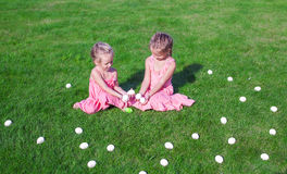 Two adorable little girls playing with Easter Eggs Stock Photo