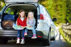 Two adorable little girls ready to go on vacations with their parents. Kids sitting in a car examining a map. Royalty Free Stock Image