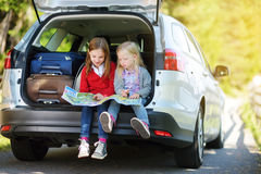 Two adorable little girls ready to go on vacations with their parents. Kids sitting in a car examining a map. Stock Photo