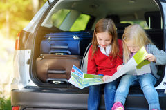 Two adorable little girls ready to go on vacations with their parents. Kids sitting in a car examining a map. Stock Images