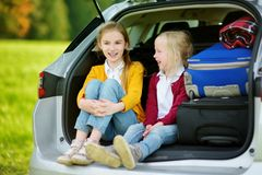Two adorable little girls sitting in a car before going on vacations with their parents. Two kids looking forward for a road trip. Or travel. Family travel by Stock Photos