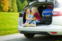 Two adorable little girls sitting in a car before going on vacations with their parents. Two kids looking forward for a road trip. Or travel. Family travel by Royalty Free Stock Photography