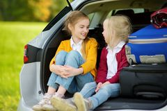 Two adorable little girls sitting in a car before going on vacations with their parents. Two kids looking forward for a road trip Royalty Free Stock Images