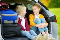 Two adorable little girls sitting in a car before going on vacations with their parents. Two kids looking forward for a road trip Royalty Free Stock Photo