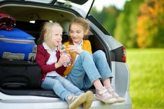 Two adorable little girls sitting in a car before going on vacations with their parents. Two kids looking forward for a road trip Royalty Free Stock Photos