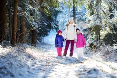 Two adorable little girls and their mother having fun together in beautiful winter park. Beautiful sisters playing in a snow. Royalty Free Stock Image