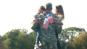 Two adorable little girls with usa backgrounds hug their father. Embracing arrived daddy, meet a hero in the park stock video footage