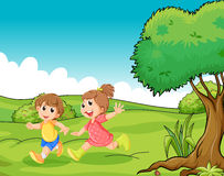Two adorable little kids playing at the hilltop near the tree Stock Photos