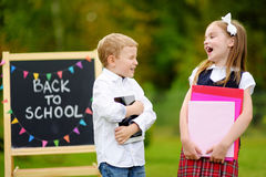 Two adorable little schoolkids feeling excited about going back to school Stock Photography