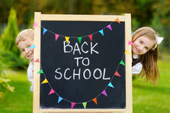 Two adorable little schoolkids feeling excited about going back to school Stock Image