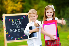 Two adorable little schoolkids feeling exited about going back to school Stock Images