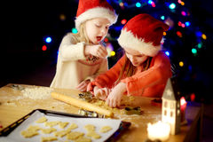 Two adorable little sisters baking Christmas cookies by a fireplace Stock Images