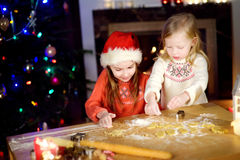 Two adorable little sisters baking Christmas cookies by a fireplace Royalty Free Stock Photos