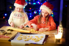 Two adorable little sisters baking Christmas cookies by a fireplace Royalty Free Stock Photo
