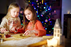 Two adorable little sisters baking Christmas cookies by a fireplace Stock Image