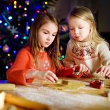Two adorable little sisters baking Christmas cookies by a fireplace Royalty Free Stock Image