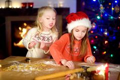 Two adorable little sisters baking Christmas cookies by a fireplace Stock Photography