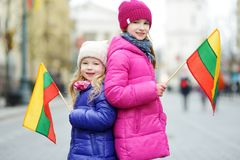 Two adorable little sisters celebrating Lithuanian Independence Day holding tricolor Lithuanian flags Royalty Free Stock Images