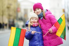 Two adorable little sisters celebrating Lithuanian Independence Day holding tricolor Lithuanian flags Royalty Free Stock Image