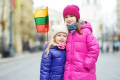 Two adorable little sisters celebrating Lithuanian Independence Day holding tricolor Lithuanian flags Stock Photos
