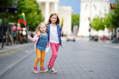 Two adorable little sisters celebrating Lithuanian Statehood Day holding tricolor Lithuanian flags in Vilnius Stock Image