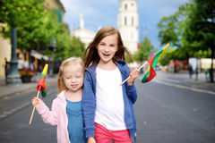 Two adorable little sisters celebrating Lithuanian Statehood Day holding tricolor Lithuanian flags in Vilnius Royalty Free Stock Photo
