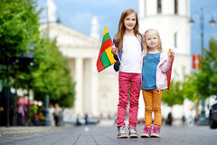Two adorable little sisters celebrating Lithuanian Statehood Day holding tricolor Lithuanian flags in Vilnius Stock Images