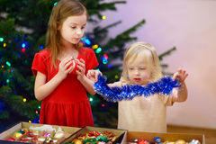 Two adorable little sisters decorating a Christmas tree Stock Photography