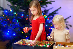 Two adorable little sisters decorating a Christmas tree Stock Photo