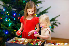Two adorable little sisters decorating a Christmas tree Stock Photos