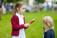 Two adorable little sisters eating an ice cream Royalty Free Stock Images