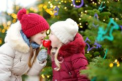 Two adorable little sisters eating red apples covered with sugar icing on traditional Christmas market. Children enjoying sweets, candies and gingerbread on Royalty Free Stock Photography