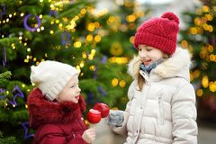 Two adorable little sisters eating red apples covered with sugar icing on traditional Christmas market Royalty Free Stock Photo