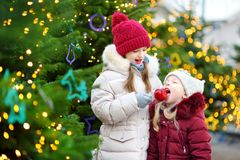 Two adorable little sisters eating red apples covered with sugar icing on traditional Christmas market Stock Images