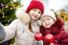 Two adorable little sisters eating red apples covered with sugar icing on traditional Christmas market Royalty Free Stock Image