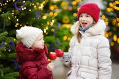 Two adorable little sisters eating red apples covered with sugar icing on traditional Christmas market Stock Photos