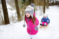Two adorable little sisters enjoying sleight ride on winter day Stock Photos