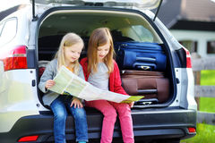 Two adorable little sisters exploring a map before going on vacations with their parents. Two kids looking forward for a road trip or travel Royalty Free Stock Photo