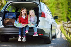 Two adorable little sisters exploring a map before going on vacations with their parents. Two kids looking forward for a road trip or travel Stock Photos