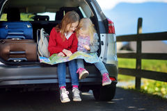 Two adorable little sisters exploring a map before going on vacations with their parents. Two kids looking forward for a road trip or travel Royalty Free Stock Photography
