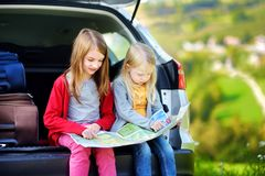 Two adorable little sisters exploring a map before going on vacations with their parents. Two kids looking forward for a road trip or travel Royalty Free Stock Images