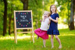 Two adorable little sisters going back to school Stock Photo